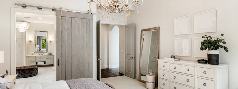 image of contemporary styled bedroom with single barn door installed as door for bathroom