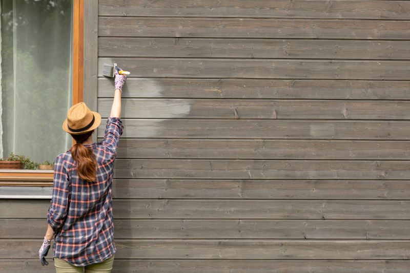 Woman worker painting wooden house exterior wall with paintbrush and wood protective color