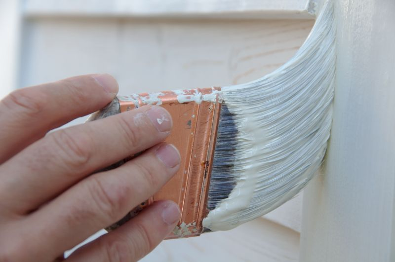 hand holding paint brush priming perpaired surface for exterior paint